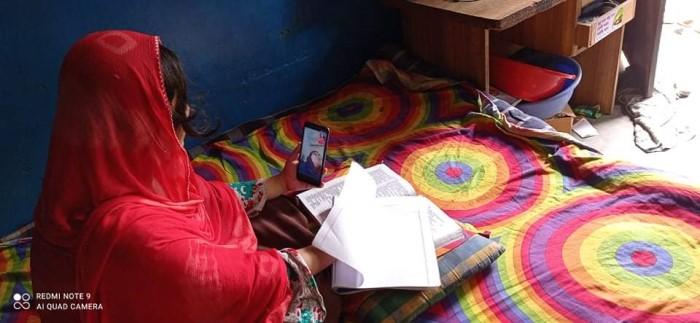 自宅でスマートフォンによりオンライン授業を受けるスラム街の子ども